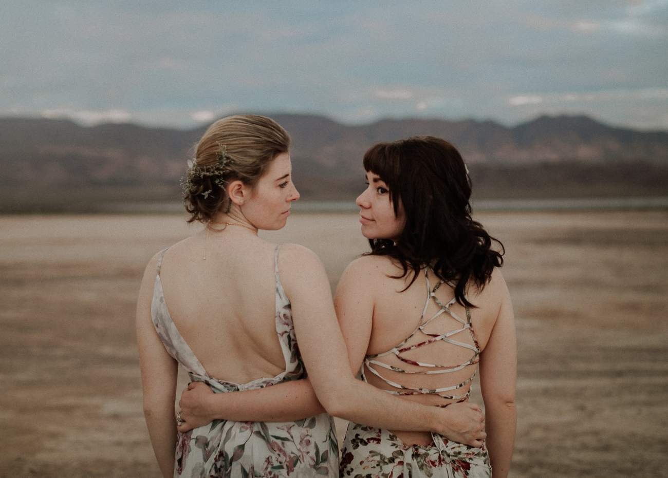 Bride and Maid of Honor look at each other at dry lake bed