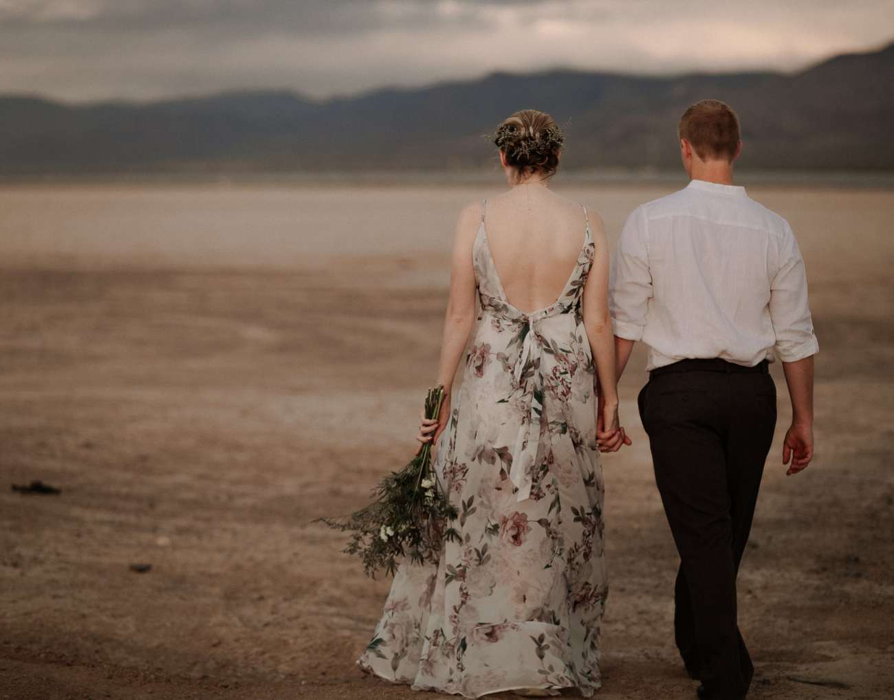 Bride and groom walk away from camera in Las Vegas Dry Lake bed at sunrise