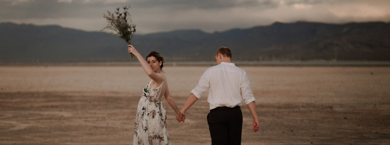 Bride and groom walking while holding hands at the Las vegas Dry Lake bed