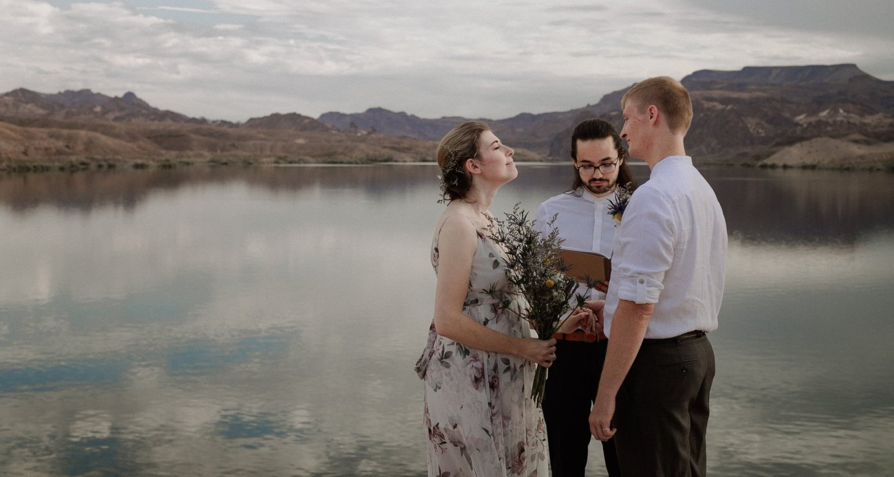 Bride and groom stand at edge of cliff over Colorado River at sunrise