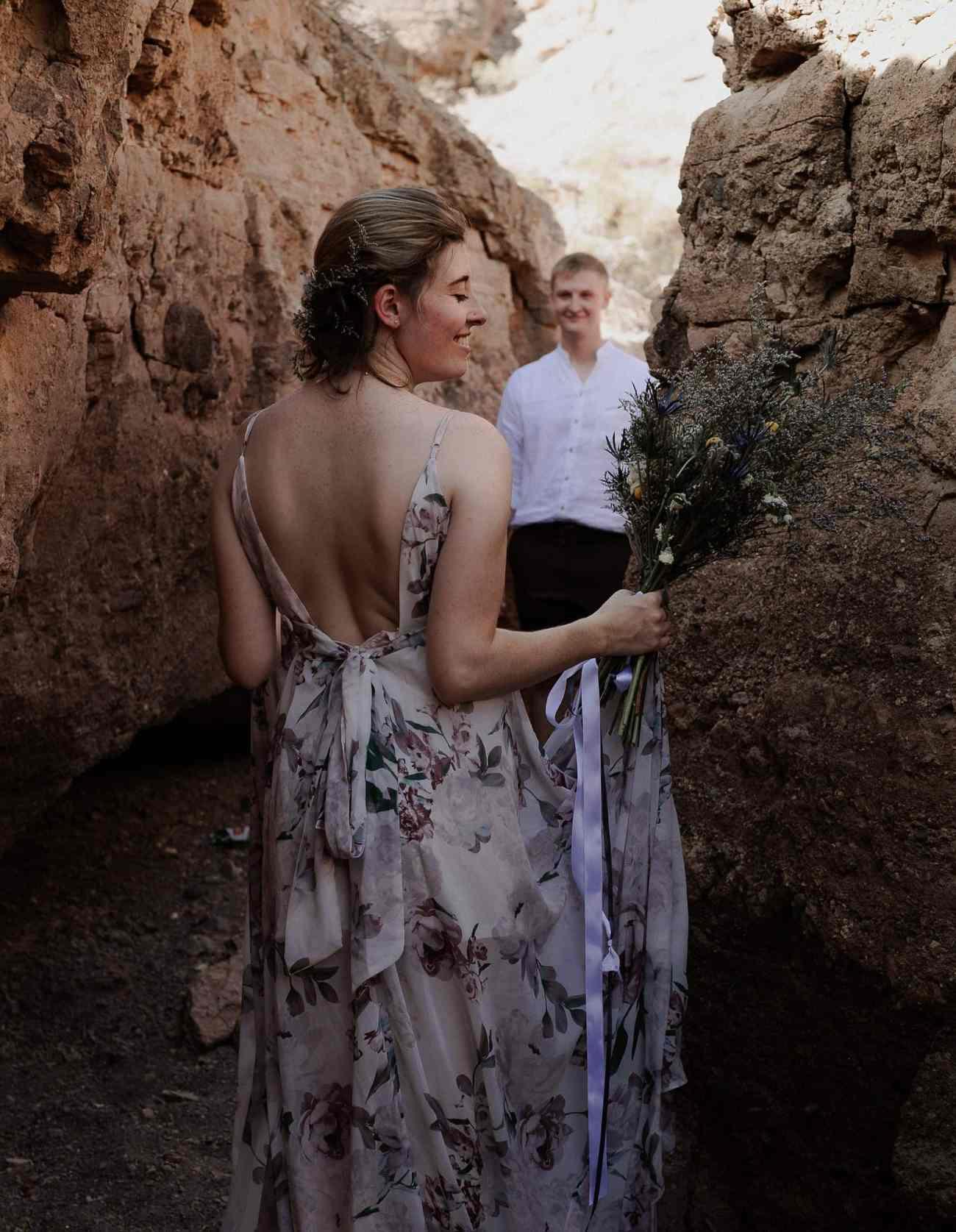 Bride and groom walk through cliffs at Nelson's Landing