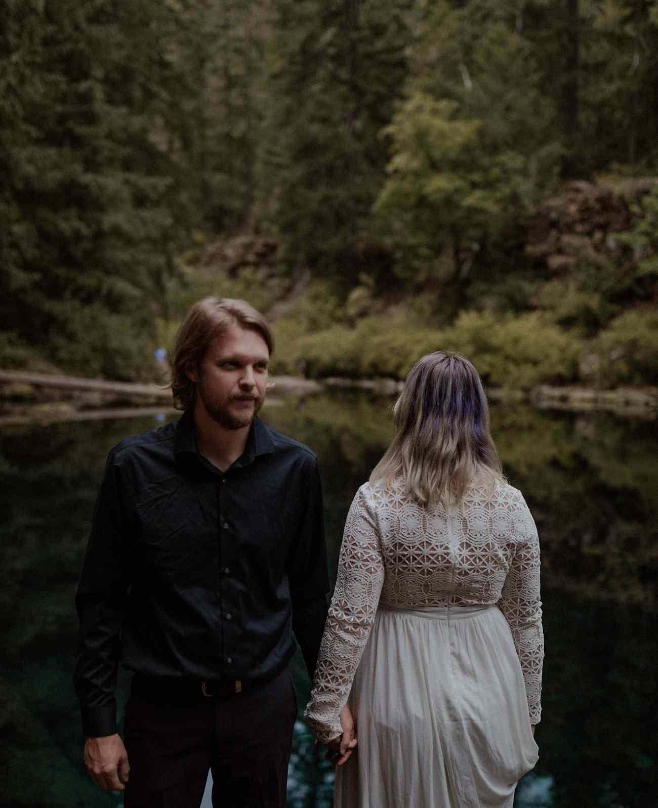 Wedding couple standing by the Blue Pool in Oregon for their portraits