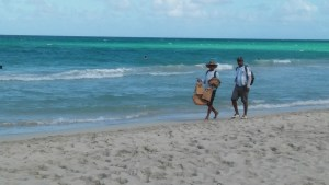 Cuban Merchants walking on the beach