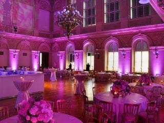 Full large hall with pink uplighting for wedding receptions
