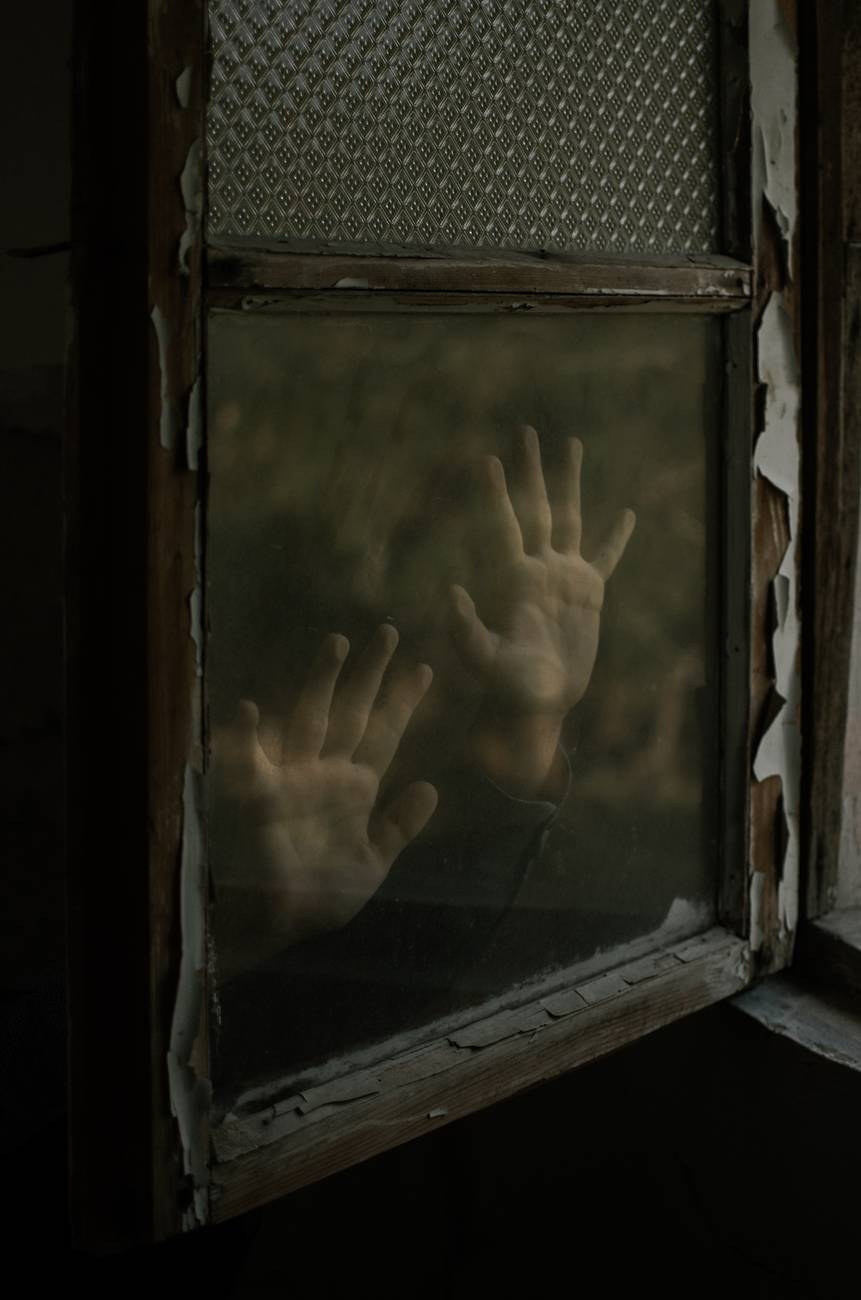 photo of person s hand on window glass