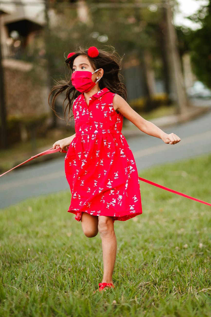 playful girl in mask running along lawn