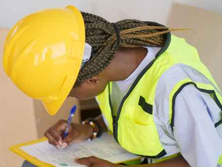 woman engineer writing down on paper