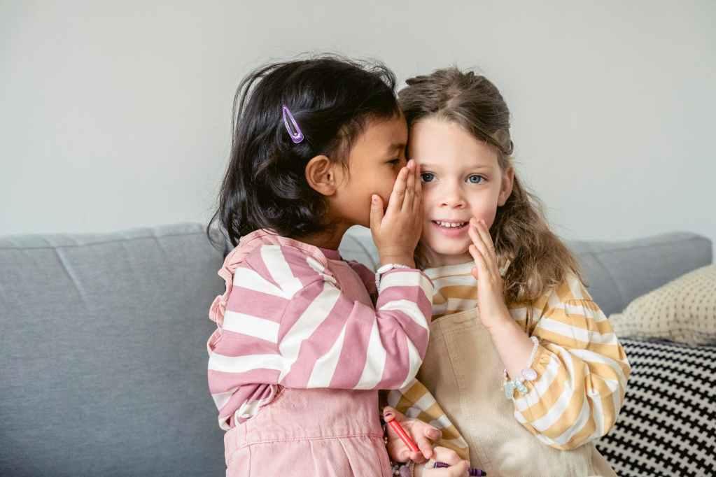 hispanic girl whispering secret on ear of friend