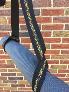 Image of blacl yoga mat strap with colorful zig zag design, holding a gray yoga mat, in front of a brick wall