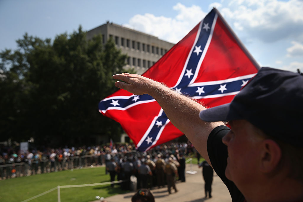 COLUMBIA, SC - JULY 18:  A member of the Ku Klux Klan gives a Nazi salute as the Klan members fly the Confederate flag during a demonstration at the state capitol building on July 18, 2015 in Columbia, South Carolina. Hundreds of people protested the demonstration as law enforcement  tried to prevent violence between the opposing groups.