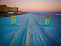New Art Titled: Beach Traffic Signs on Daytona Beach at Dawn. Photo art edit of beach traffic lanes, speed limit and caution signs, the traffic patterns in the sand, the ocean to the right and the resorts on the right