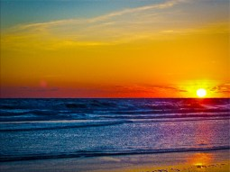 New Art Titled: Sunrise Over Atlantic Ocean & Water Reflection III. Beautiful photography digital edit as the sun rises above the coastline of the Atlantic Ocean seascape artwork, with golden reflection in waterline at the edge of ocean on beach.
