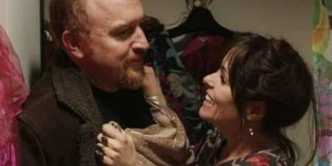 Liz a.k.a Tape Recorder (Parker Posey) coerces Louie into trying on a sparkly dress for her amusement.