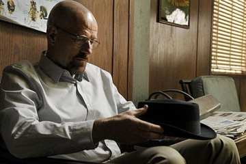 Walter White (the glorious Bryan Cranston) pulls at the symbolic loose thread of his Heisenberg hat