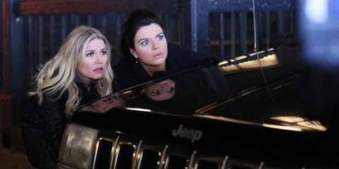 Alex (Elisha Cuthbert) and Penny (Casey Wilson) watch a pop stars breakdown.