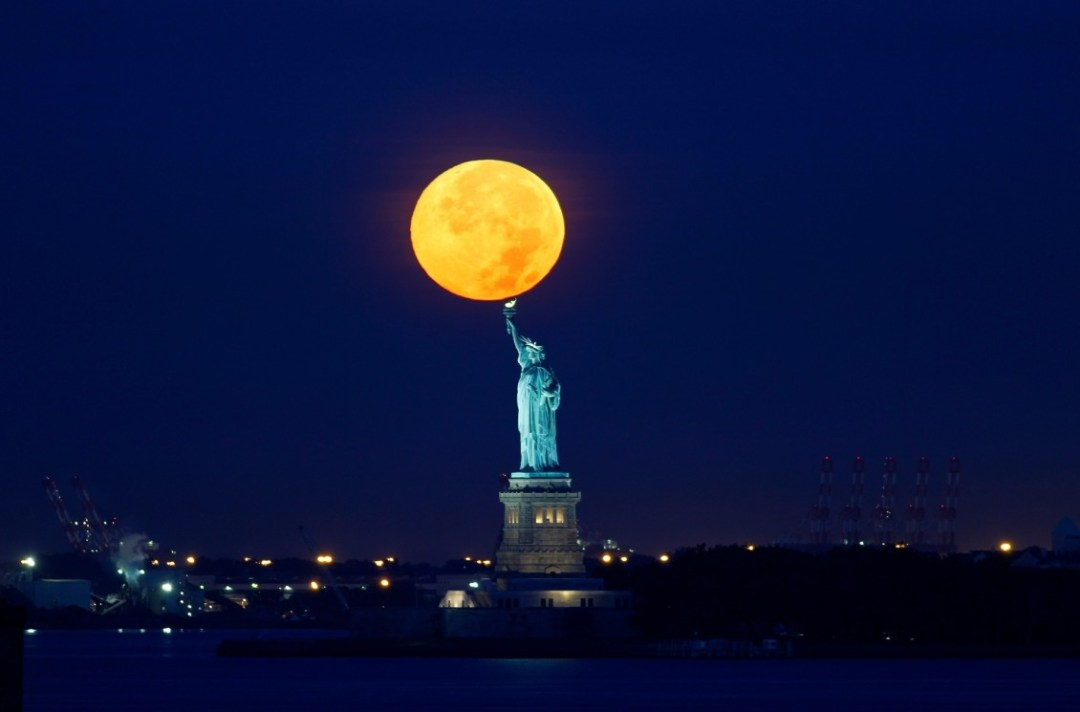 A supermoon sets behind the Statue of Liberty, New York in 2015. (Credit: Gary Hershorn/Corbis)