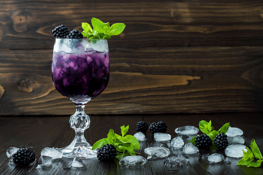 blackberry cocktail in wine glass with mint