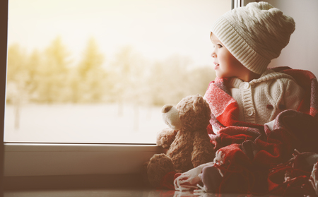little girl sitting by the window with a teddy bear
