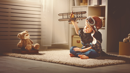 aviator child with a toy airplane plays at home in his room