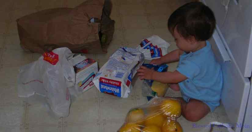 Take inventory of what you have before you go plan your meals or go to the grocery store. Image of a toddler boy sitting on the kitchen floor helping to unload grocery bags.