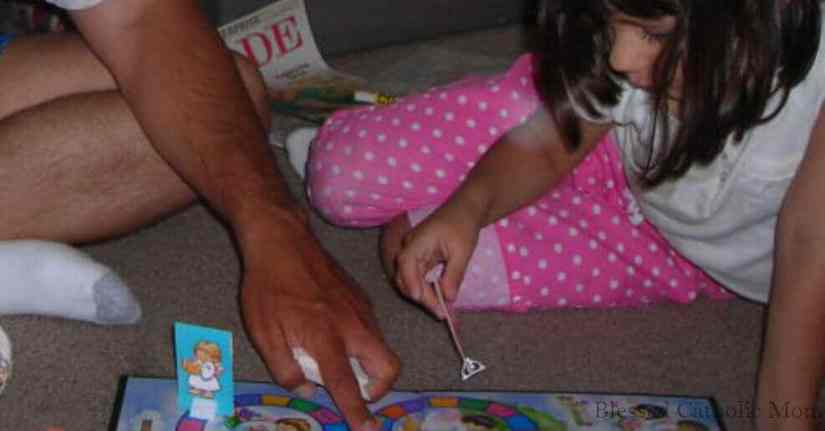 Plan time together with your children. Image of father and daughter playing a board game while sitting on the floor.