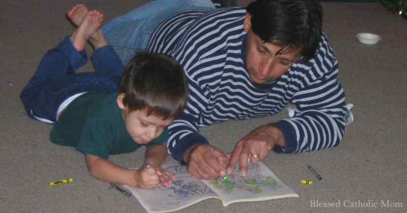 We need to spend intentional time with our children. Image of a young son and father laying on the floor coloring in a coloring book.