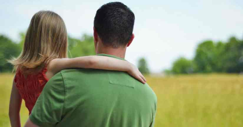 My husband does not babysit our kids; he parents them. Image of a father holding daughter-view from behind them