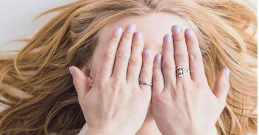 We use the word just as an excuse not to try our best. Yo are not just a mom. Image of a woman holding her hands over her eyes.