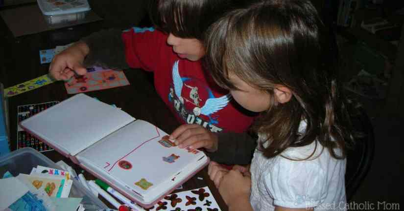 Kids working on a scrapbook together.