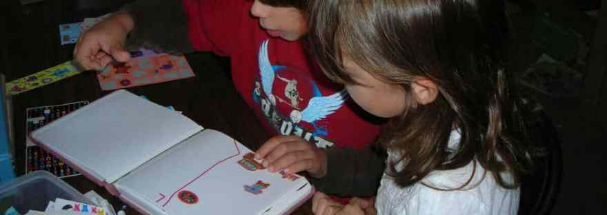 Keeping (or not) kids' memorabilia and keepsakes. Image of a boy and a girl working on a scrapbook together.