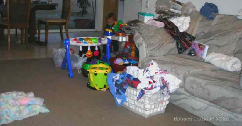 House cleaning does not need to be an overwhelming task. Follow these five simple steps with your family to have a better mindset and a neater home. Image of a room with a lot of toys, an overflowing laundry basket, and a couch cluttered with items. Blessed Catholic Mom watermark on photo at the bottom.