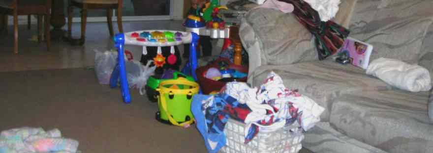 House cleaning does not need to be an overwhelming task. Just work some each day to get things done. Image of a room with a lot of toys, an overflowing laundry basket, and a couch cluttered with items. Blessed Catholic Mom watermark on photo at the bottom.