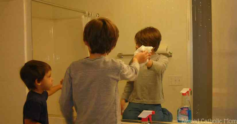 House cleaning does not need to be an overwhelming task. Work together as a family. Image of a boy cleaning a bathroom mirror while his younger brother looks on.