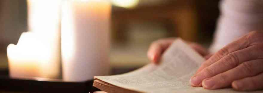 Learning how to pray in the way of Lectio Divina is not difficult. Here are the five simple steps to get you started. Image of a an open Bible with a hand about to turn the page. A lit candle in the background.
