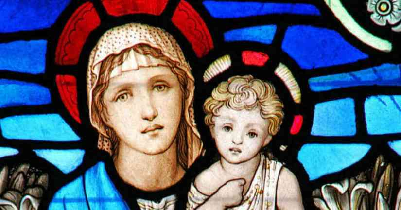 The saints are our friends. More than our friends, they are our family in Christ. We can ask them to pray for us. Image of a stained glass window: Mary holding the infant Jesus.