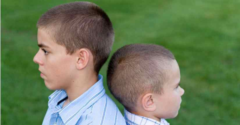 Parenting is on the job training. It is our job to help our kids learn to deal with their siblings as well as with others. Image of two boys back to back.