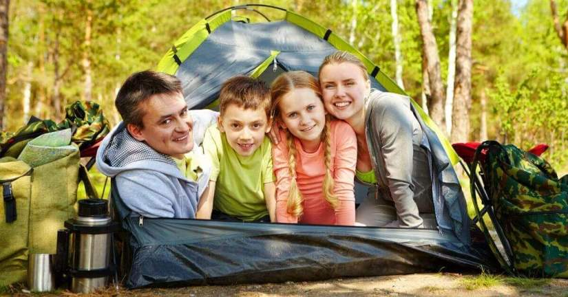 Here are tips to make family dinners happen and enjoyable. Create a special time together to have fun, learn more about each other, and plan together. While you eat, make plans to do something fun as s a family. Image of a family inside of a tent looking out and smiling at the camera.