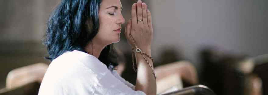 It can be challenging to live as God wants me to live on a daily basis. How do I know how God wants me to live each day? Ephesians, St. Paul tells us. Image of woman holding a Rosary and praying at church.