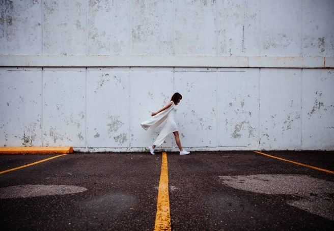 Rejected woman in white walking briskly