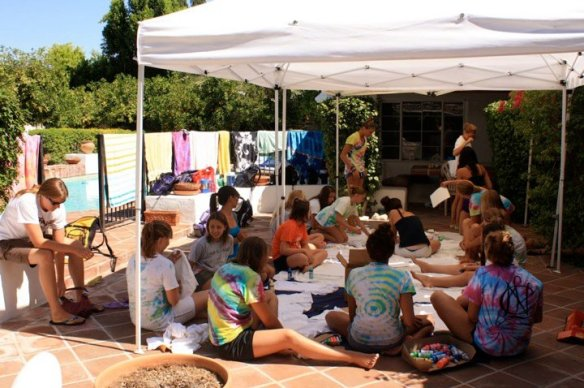 Swim team girls painting t-shirts for a meet in our back yard with their coach.