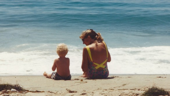 mom and toddler son sitting on the beach