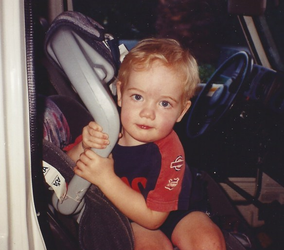 blond toddler in his car seat