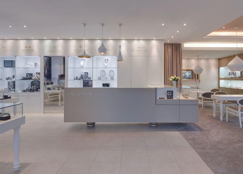 """Insgesamt ist der Raum dezent durch Form- und Farbwechsel in zwei Bereiche aufgeteilt: eine helle geflieste Seite mit weißen Vitrinen für die """"Charme-Mode"""", und für das Exklusiv-Sortiment farbintensiver mit Teppich und Wandschrank in Bronze."""