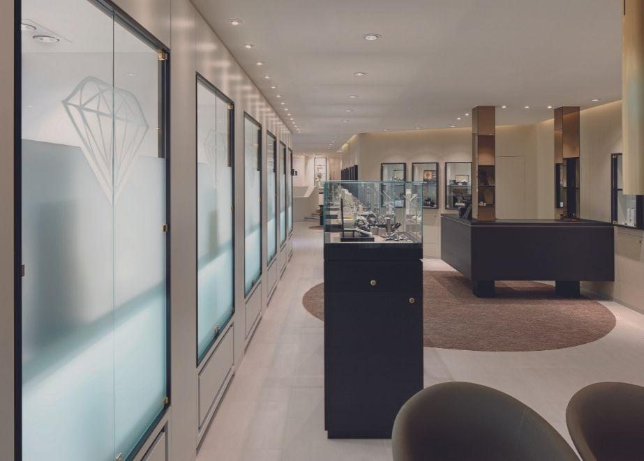Das Ladendesign im Erdgeschoss bei Juwelier Stroh in Backnang bei Stuttgart ist hell und freundlich gestaltet. Dunkle, kubische Vitrinen lassen klare Raumachsen ent-stehen und die Innenarchitektur wirken. Die schlichten, puren Möbelformen und deren axiale Anordnung vermitteln eine elegante und wertige Atmosphäre.