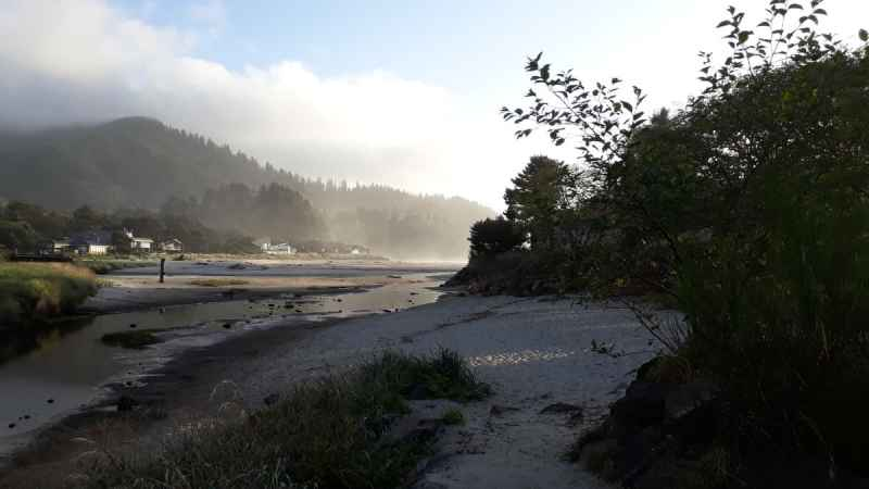 Photo of a sunny afternoon at Neskowin, a cloud resting on the hills in the distance