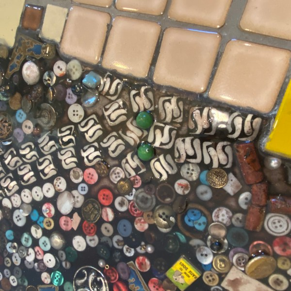 A detail of the tile floor next to multi media objects suspended in tinted epoxy