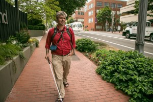 A man with a cane and carrying assistive technology walks down a downtown Portland street.