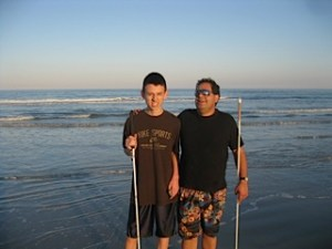 A visually impaired boy and man stand on the beach with the ocean behind them.