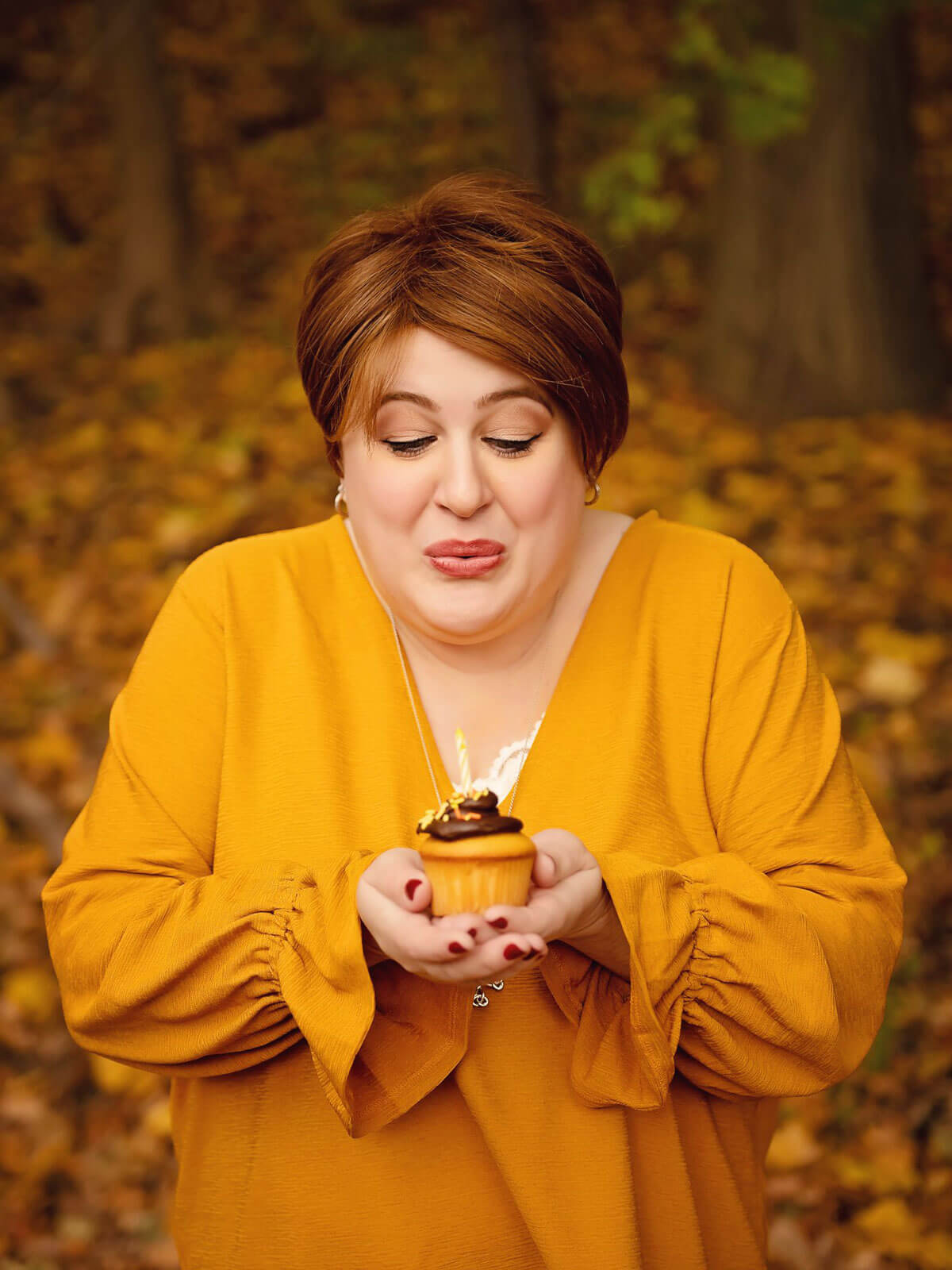 Holly wearing a marigold color sweater and blowing out a single candle on a cupcake.
