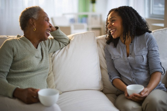 Jersey City, New Jersey, USA --- Mother and daughter talking and drinking coffee on sofa --- Image by © JGI/Tom Grill/Blend Images/Corbis